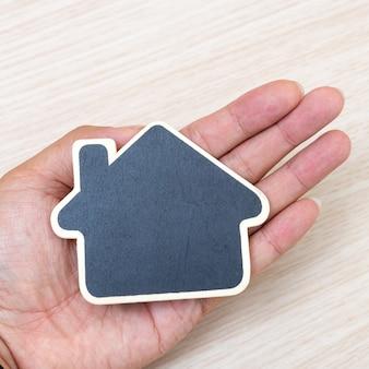 Klein houten huis bij de hand. concept voor onroerende goederenzaken.