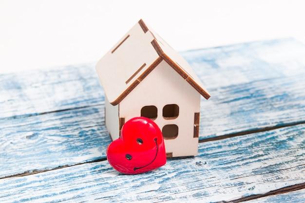 Klein houten huis en hart op blauwe houten achtergrond, kopieer ruimte
