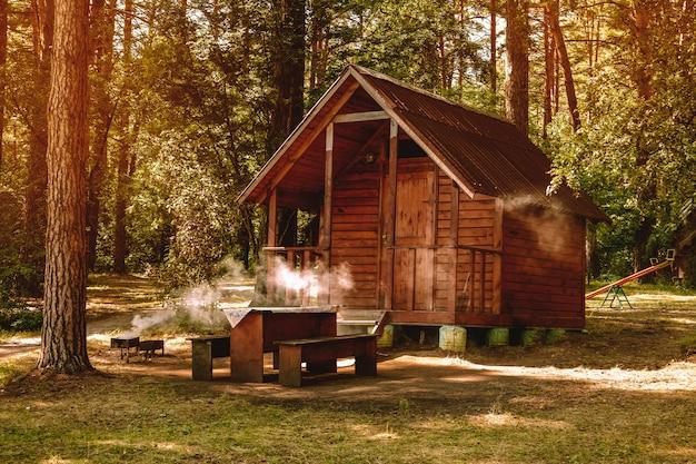 Klein houten huis in een dennenbos voor recreatie, kamperen in het bos, barbecue in de natuur