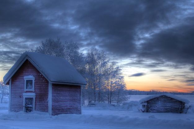 Klein houten huis in het veld bedekt met sneeuw tijdens zonsondergang