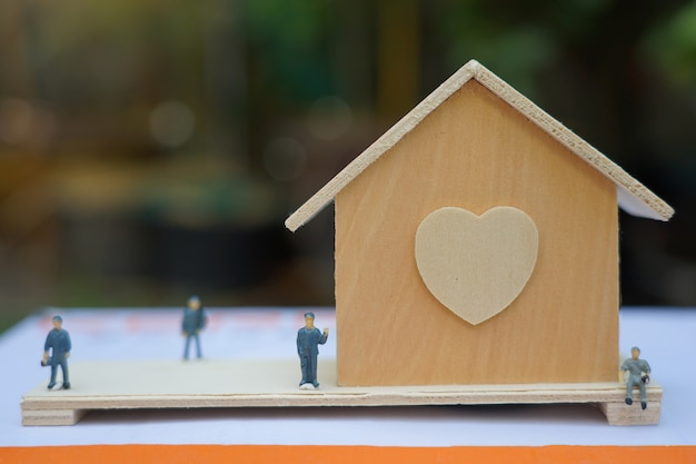Klein houten huis met beeldjes dichtbij
