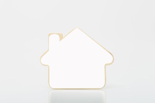 Klein houten huis met witte blanco op tabel. concept voor onroerende goederenzaken.