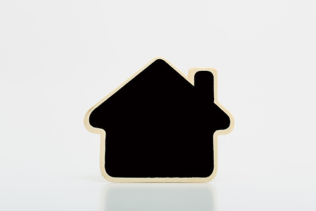 Klein houten huis met zwarte spatie op tabel. concept voor onroerende goederenzaken.