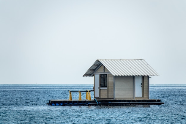 Klein houten huisje gelegen in het water van de oceaan