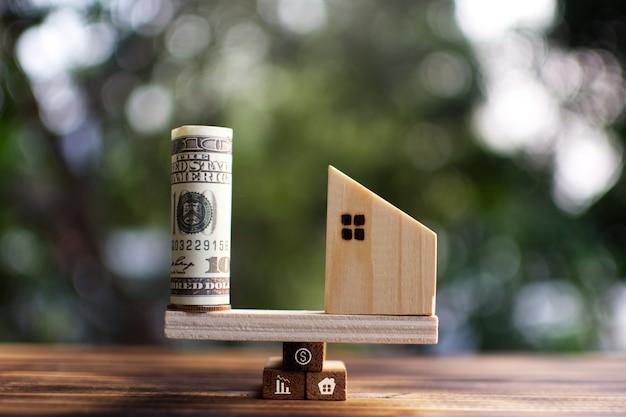 Klein houten huismodel en bankbiljet op plankbegin om de woonwijk te beschermen.