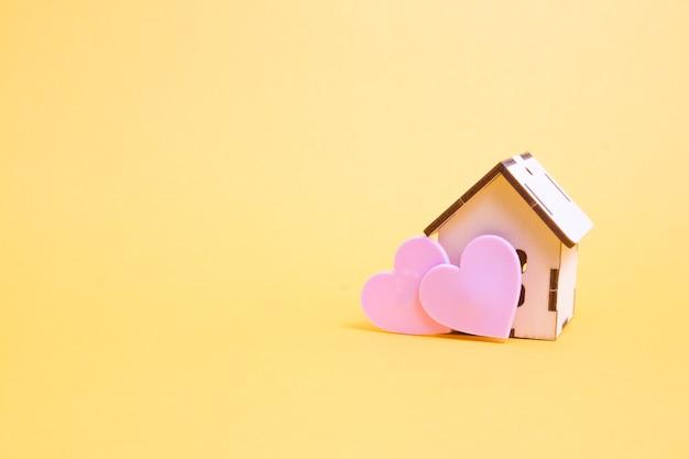 Klein houten huismodel en twee roze harten op een gele achtergrond