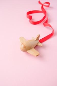 Klein houten speelgoedvliegtuig draagt rood lint in de vorm van een hart