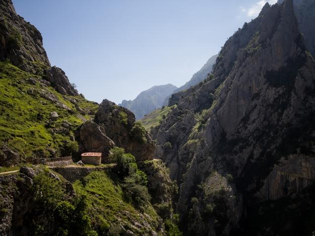 Klein huis aan de rand van de afgrond in enorme bergen