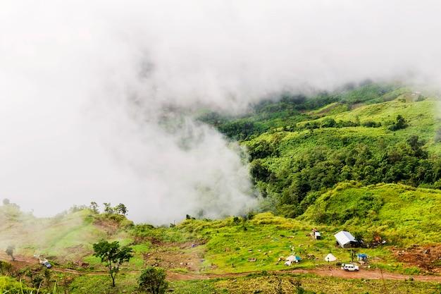 Klein huis aan de voet van de berg in de ochtendmist.