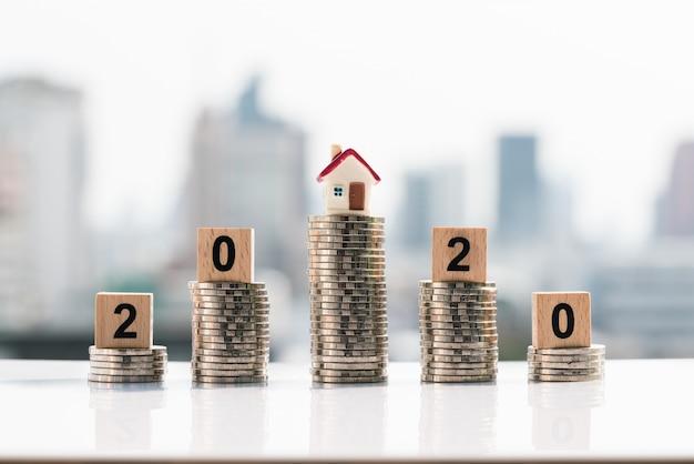 Klein huis en 2020 houten blokken bovenop muntstapel op stadsachtergronden.