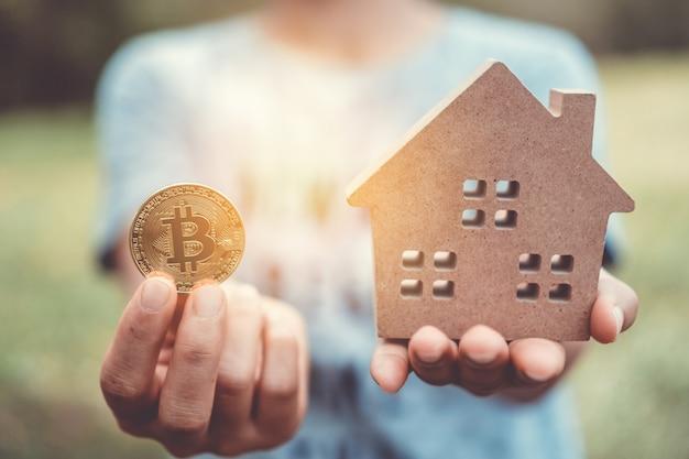 Klein huis en een symbool van cryptocurrency. droomleven hebben eigen huiseigendom voor wonen of beleggen.
