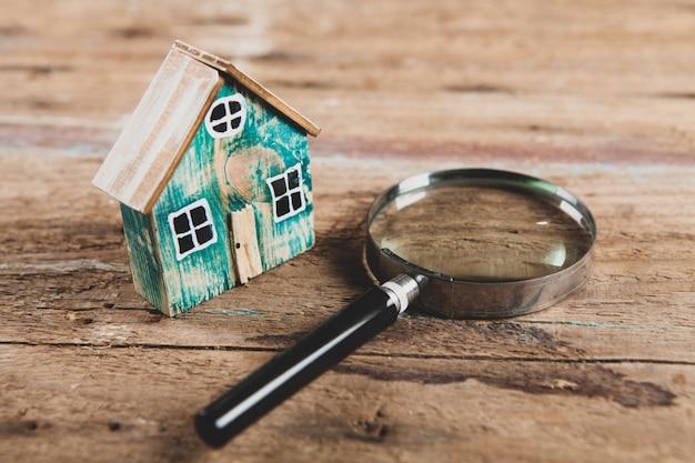 Klein huis en een vergrootglas op een houten tafel