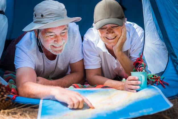 Klein huis in het bos voor een paar gelukkige en vrolijke man en vrouw van volwassen gepensioneerden. glimlach op zoek naar de kaart voor de volgende stap in hun alternatieve leven en reis voor altijd samen