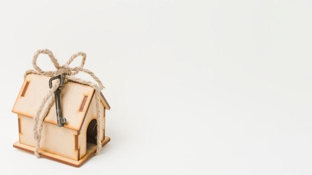 Klein huismodel dat met koord en uitstekende sleutel wordt gebonden die met witte achtergrond wordt geïsoleerd
