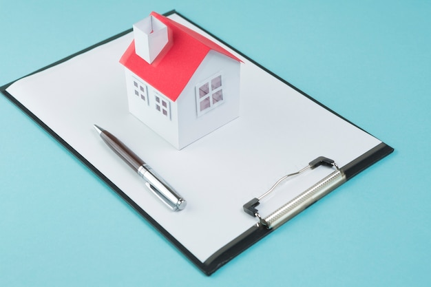 Klein huismodel en pen op leeg klembord over blauwe achtergrond