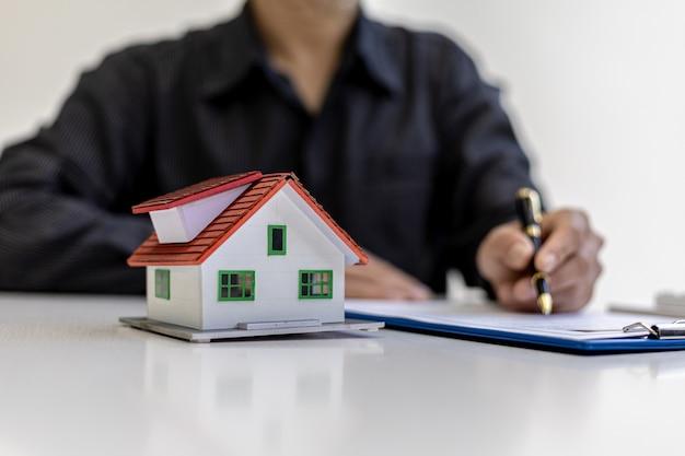 Klein huismodel op het bureau geplaatst, zakenmensen wonen vergaderingen bij met verkoopmanagers om verkoop en promoties te plaatsen, marketingplannen om meer omzet te genereren. verkoopbeheerconcept.