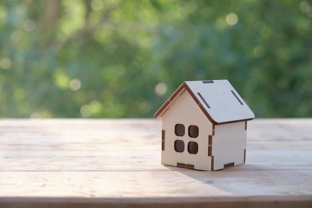 Klein huismodel op houten tafel met natuur groene bokeh abstracte achtergrond. gezinsleven en zakelijk onroerend goed concept.