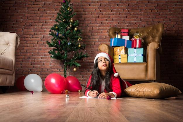 Klein indiaas aziatisch meisje schrijft met kerst een brief aan de kerstman terwijl ze thuis op de vloer zit met cadeaus op de achtergrond