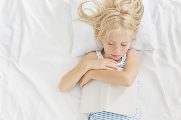 Klein jong geitje met mooie verschijning die na het lezen van interessante verhalen in bed slapen, boek in handen houden, liggend op wit hoofdkussen en bedkleren, prettige dromen hebben. lezen voor het slapen gaan