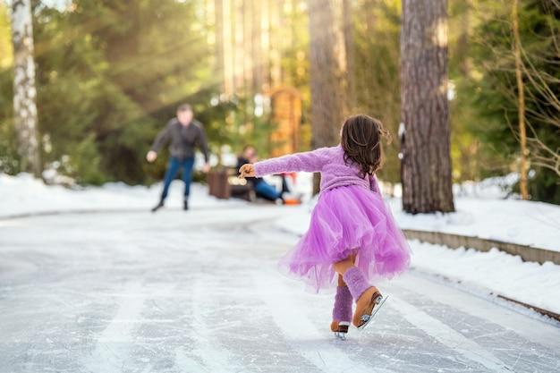 Klein jong meisje in een roze trui en een volle rok rijdt op een zonnige winterdag op een buitenijsbaan in het park