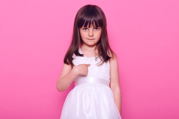 Klein kalm charmant meisje dat een mooie witte jurk draagt die naar voren kijkt met een beetje verlegen uitdrukking, naar zichzelf wijzend met wijsvinger, geïsoleerd over roze muur