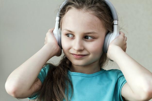 Klein kaukasisch meisje dat in hoofdtelefoons aan muziek op lichte achtergrond luistert. draadloze koptelefoon