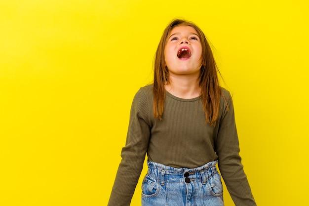 Klein kaukasisch meisje dat op geel wordt geïsoleerd dat zeer boos, gefrustreerd woedeconcept schreeuwt.