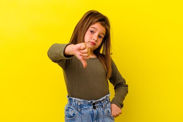 Klein kaukasisch meisje dat op geel wordt geïsoleerd die duim neer, teleurstellingconcept toont.