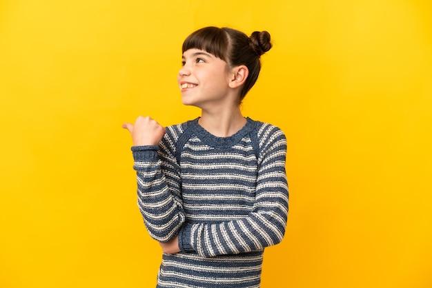 Klein kaukasisch meisje dat op gele achtergrond wordt geïsoleerd die naar de kant wijst om een product te presenteren