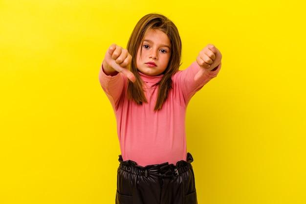 Klein kaukasisch meisje dat op gele muur wordt geïsoleerd die duim toont en afkeer uitdrukt.
