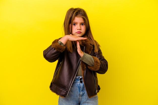 Klein kaukasisch meisje dat op gele muur wordt geïsoleerd die een time-outgebaar toont.