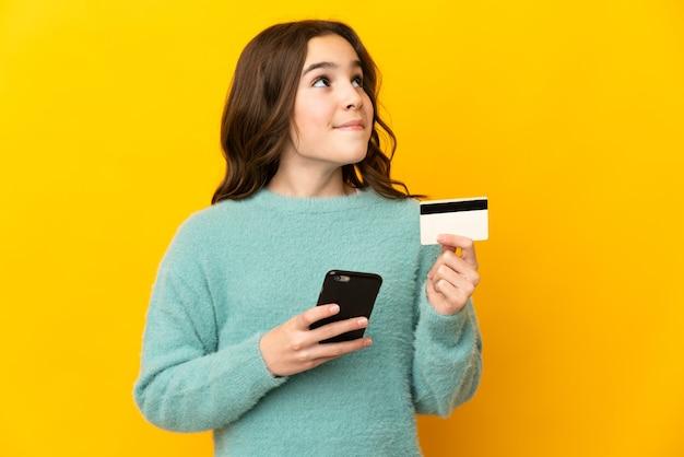 Klein kaukasisch meisje dat op gele muur wordt geïsoleerd die met mobiel met een creditcard koopt terwijl het nadenken