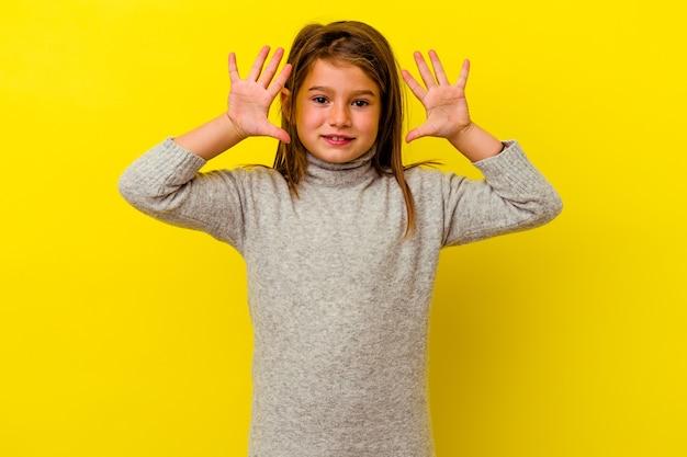 Klein kaukasisch meisje dat op gele muur wordt geïsoleerd die nummer tien met handen toont.