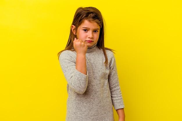 Klein kaukasisch meisje dat op gele muur wordt geïsoleerd die vuist toont aan camera, agressieve gezichtsuitdrukking.