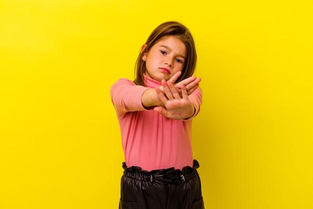Klein kaukasisch meisje dat op gele status met uitgestrekte hand wordt geïsoleerd die stopbord toont, dat u verhindert.