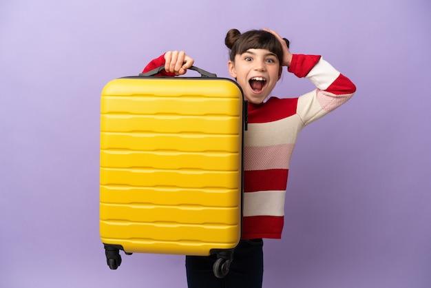 Klein kaukasisch meisje dat op purpere muur in vakantie met reiskoffer wordt geïsoleerd en verrast