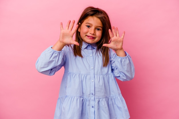 Klein kaukasisch meisje dat op roze muur wordt geïsoleerd die nummer tien met handen toont.