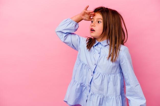Klein kaukasisch meisje dat op roze muur wordt geïsoleerd die ver weg kijkt die hand op voorhoofd houdt.