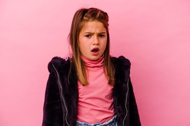 Klein kaukasisch meisje dat op roze muur wordt geïsoleerd die zeer boos en agressief gilt.