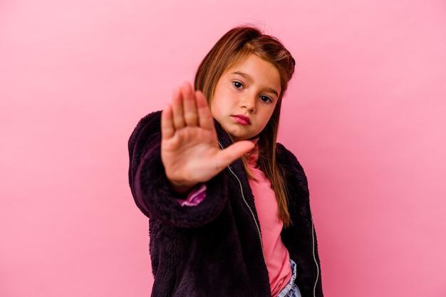 Klein kaukasisch meisje dat op roze status met uitgestrekte hand wordt geïsoleerd die stopbord toont, dat u verhindert.