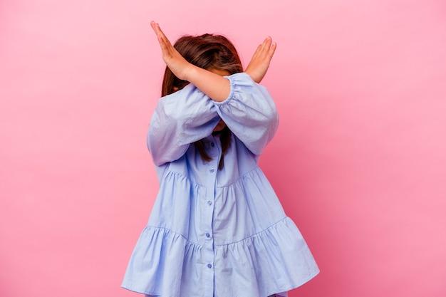 Klein kaukasisch meisje dat op roze wordt geïsoleerd die twee gekruiste wapens, ontkenningsconcept houdt.