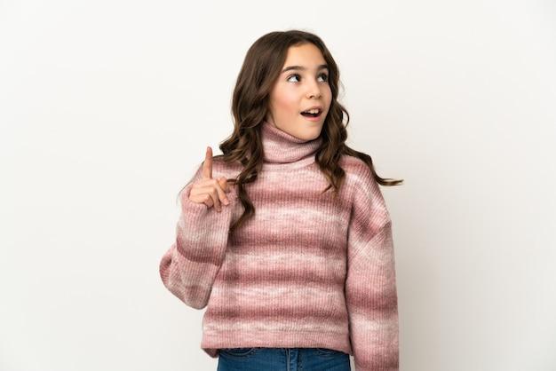 Klein kaukasisch meisje dat op witte muur wordt geïsoleerd die een idee denkt dat de vinger omhoog richt