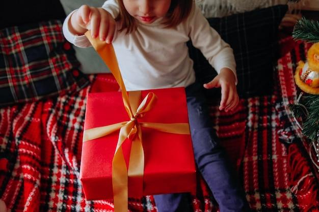 Klein kaukasisch meisje dat plezier heeft met huisdierdecoraties en cadeausconcept nieuwjaarsconcept
