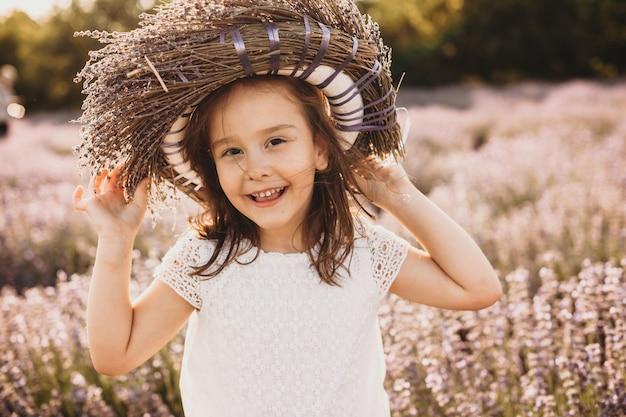 Klein kaukasisch meisje die vrolijk op lavendelgebied stellen met een bloemkroon op hoofd