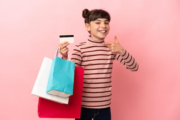 Klein kaukasisch meisje geïsoleerd bedrijf boodschappentassen en een creditcard