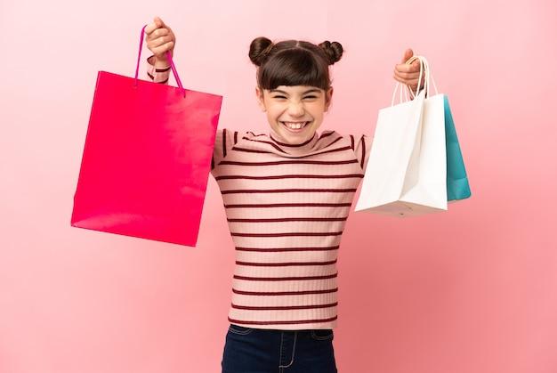 Klein kaukasisch meisje geïsoleerd bedrijf boodschappentassen en glimlachen