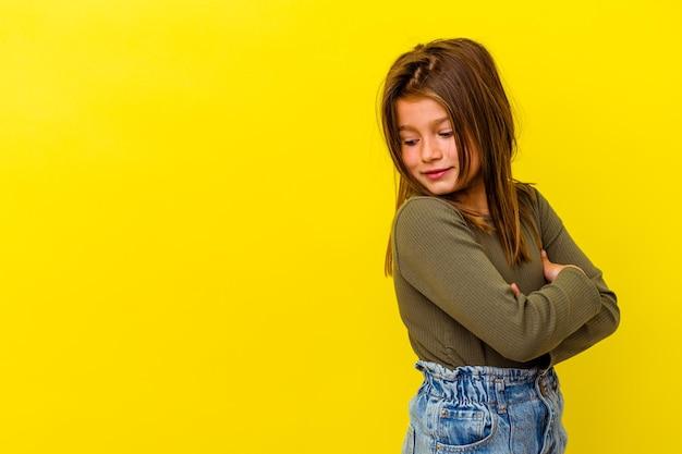 Klein kaukasisch meisje geïsoleerd op geel glimlachend zelfverzekerd met gekruiste armen.