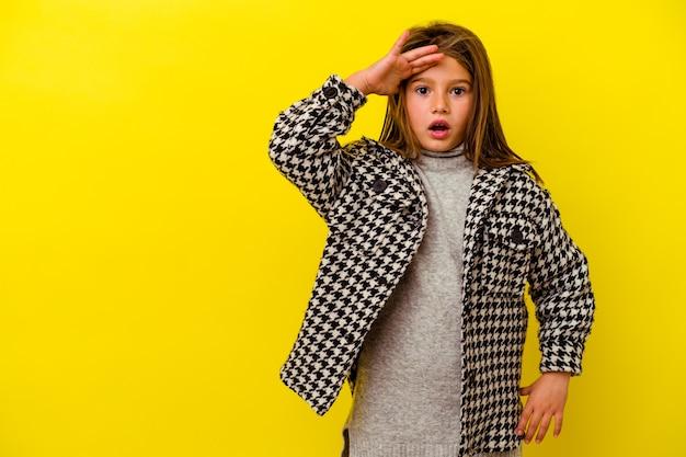 Klein kaukasisch meisje geïsoleerd op geel schreeuwt luid, houdt ogen open en handen gespannen.