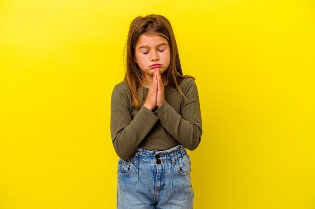 Klein kaukasisch meisje geïsoleerd op gele muur bidden, toewijding tonen, religieuze persoon op zoek naar goddelijke inspiratie.