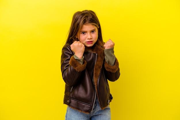 Klein kaukasisch meisje geïsoleerd op gele muur boos schreeuwen met gespannen handen.